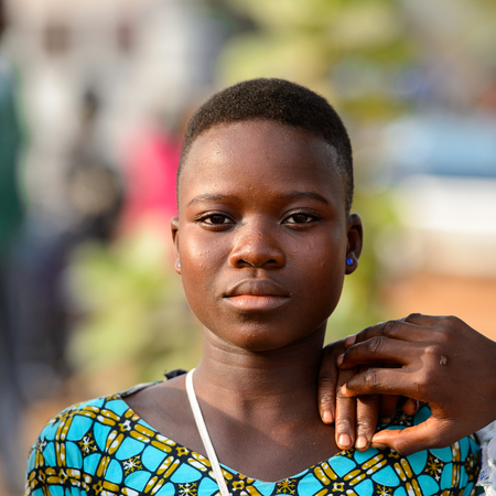 OUIDAH, BENIN - Jan 10, 2017: Unidentified Beninese beautiful girl in colored shirt wears earings at the local market. Benin people suffer of poverty due to the bad economy
