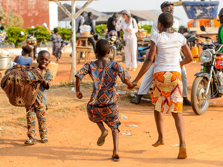 OUIDAH, BENIN - Jan 10, 2017: Unidentified Beninese  little girls from behind at the voodoo festival, which is anually celebrated on January, 10th.