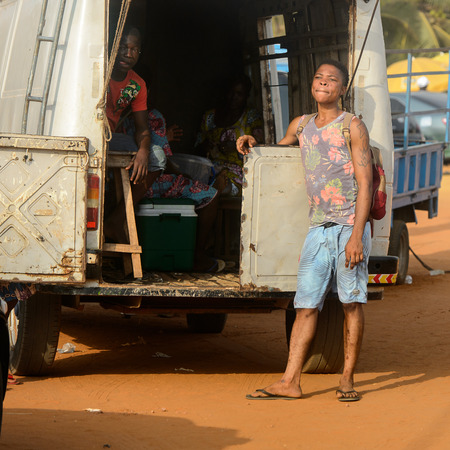 OUIDAH, BENIN - Jan 10, 2017: Unidentified Beninese boy leans on the car at the local market. Benin people suffer of poverty due to the bad economy