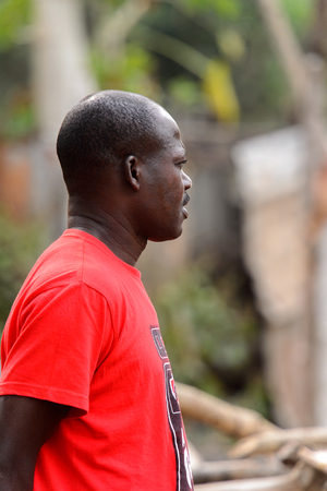 KUMASI, GHANA - Jan 16, 2017: Unidentified Ghanaian man in red shirt with mustaches looks away. People of Ghana suffer of poverty due to the bad economy Editorial