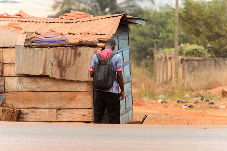 KUMASI, GHANA - Jan 16, 2017: Unidentified Ghanaian man with backpack from behind stands near the shack. People of Ghana suffer of poverty due to the bad economy