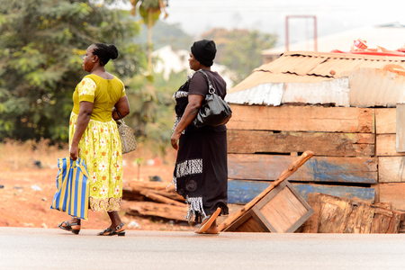 KUMASI, GHANA - Jan 16, 2017: Unidentified Ghanaian women walk along the road. People of Ghana suffer of poverty due to the bad economy