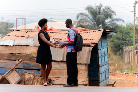 KUMASI, GHANA - Jan 16, 2017: Unidentified Ghanaian two people talk near the shack. People of Ghana suffer of poverty due to the bad economy