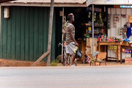 KUMASI, GHANA - Jan 16, 2017: Unidentified Ghanaian man in striped shirt with plastic bag walks by the shop. People of Ghana suffer of poverty due to the bad economy