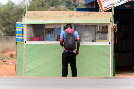 KUMASI, GHANA - Jan 16, 2017: Unidentified Ghanaian man stands near the stall from behind with backpack. People of Ghana suffer of poverty due to the bad economy