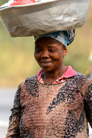 KUMASI, GHANA - Jan 16, 2017: Unidentified Ghanaian woman carries a basin on her head and smiles. People of Ghana suffer of poverty due to the bad economy Éditoriale