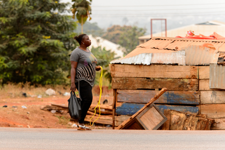KUMASI, GHANA - Jan 16, 2017: Unidentified Ghanaian woman walks along the road with plastic bag and skipping rope. People of Ghana suffer of poverty due to the bad economy Editorial