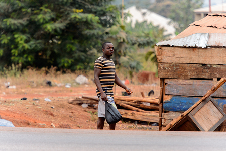 KUMASI, GHANA - Jan 16, 2017: Unidentified Ghanaian man  in striped shirt walks along the road with plastic bag. People of Ghana suffer of poverty due to the bad economy