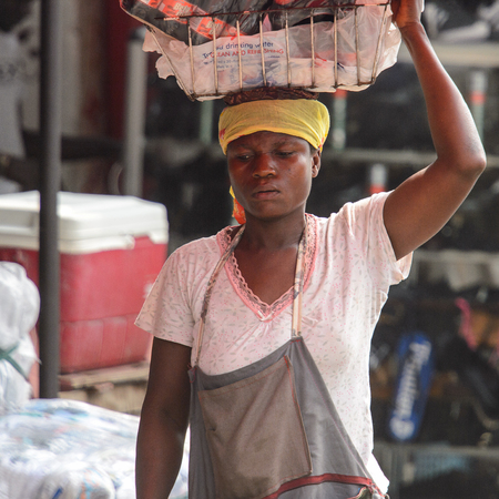 KUMASI, GHANA - Jan 16, 2017: Unidentified Ghanaian woman carries a basket on her head. People of Ghana suffer of poverty due to the bad economy