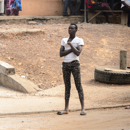 KUMASI, GHANA - Jan 16, 2017: Unidentified Ghanaian man in white shirt and leggings crosses his hands. People of Ghana suffer of poverty due to the bad economy