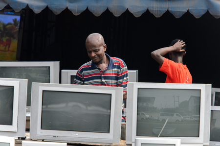 KUMASI, GHANA - Jan 16, 2017: Unidentified Ghanaian man in striped shirt stands behind TV sets. People of Ghana suffer of poverty due to the bad economy Editorial