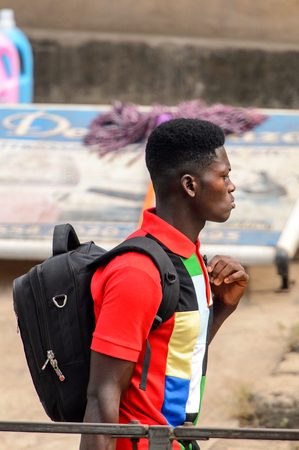 KUMASI, GHANA - Jan 16, 2017: Unidentified Ghanaian young man walks with backpack . People of Ghana suffer of poverty due to the bad economy