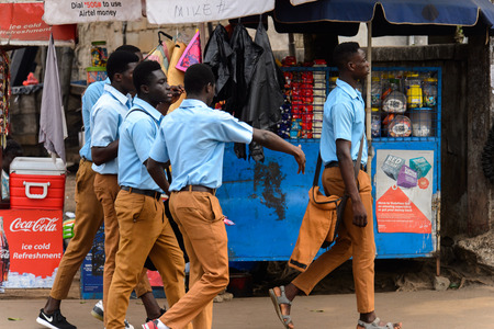 KUMASI, GHANA - Jan 16, 2017: Unidentified Ghanaian students in blue shirts and mustard pants walk on the street. People of Ghana suffer of poverty due to the bad economy Editorial