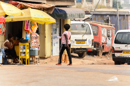 KUMASI, GHANA - Jan 16, 2017: Unidentified Ghanaian woman with braids from behind walks to the shop. People of Ghana suffer of poverty due to the bad economy