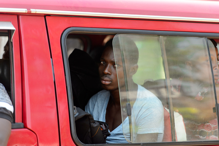 CENTRAL REGION, GHANA - Jan 17, 2017: Unidentified Ghanaian man looks out of the red car's window in local village. People of Ghana suffer of poverty due to the bad economy