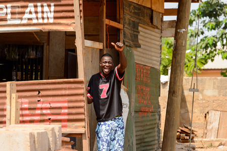 CENTRAL REGION, GHANA - Jan 17, 2017: Unidentified Ghanaian man in black shirt smiles in local village. People of Ghana suffer of poverty due to the bad economy Editoriali