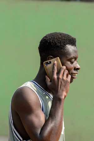 CENTRAL REGION, GHANA - Jan 17, 2017: Unidentified Ghanaian man talks on cellphone in local village. People of Ghana suffer of poverty due to the bad economy