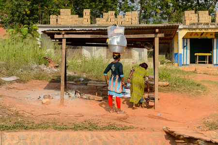 CENTRAL REGION, GHANA - Jan 17, 2017: Unidentified Ghanaian woman carries a basin on her head in local village. People of Ghana suffer of poverty due to the bad economy