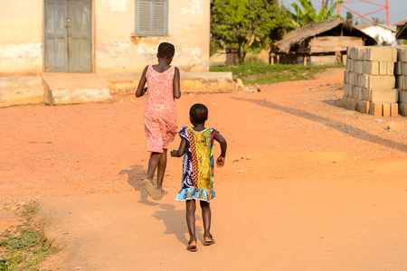 CENTRAL REGION, GHANA - Jan 17, 2017: Unidentified Ghanaian woman and little girl from behind in local village. People of Ghana suffer of poverty due to the bad economy Editoriali