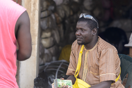 CENTRAL REGION, GHANA - Jan 17, 2017: Unidentified Ghanaian man holds a pack of money in local village. People of Ghana suffer of poverty due to the bad economy