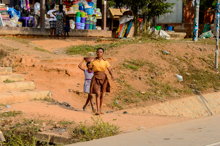 CENTRAL REGION, GHANA - Jan 17, 2017: Unidentified Ghanaian two girls walk along the street in local village. People of Ghana suffer of poverty due to the bad economy Editorial
