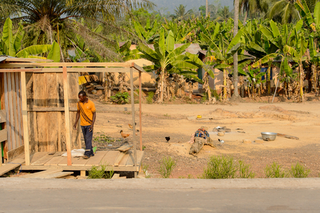CENTRAL REGION, GHANA - Jan 17, 2017: Unidentified Ghanaian man in orange shirt looks down in local village. People of Ghana suffer of poverty due to the bad economy