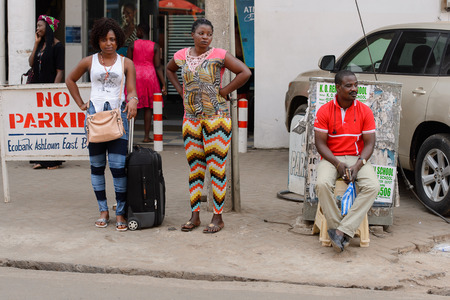 CENTRAL REGION, GHANA - Jan 17, 2017: Unidentified Ghanaian two women stand beside the road with luggage in local village. People of Ghana suffer of poverty due to the bad economy
