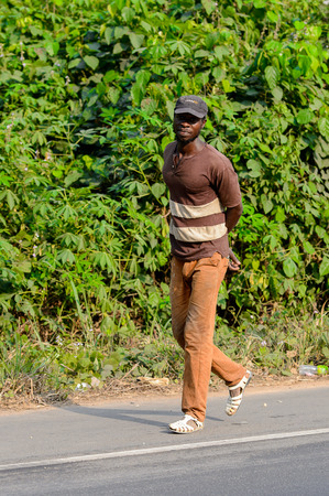 CENTRAL REGION, GHANA - Jan 17, 2017: Unidentified Ghanaian man walks along the road in local village. People of Ghana suffer of poverty due to the bad economy