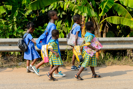 CENTRAL REGION, GHANA - Jan 17, 2017: Unidentified Ghanaian pupils walk along the road in local village. People of Ghana suffer of poverty due to the bad economy Editorial