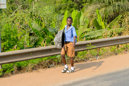 CENTRAL REGION, GHANA - Jan 17, 2017: Unidentified Ghanaian pupils walk along the street in local village. Children of Ghana suffer of poverty due to the bad economy