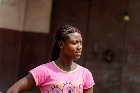CENTRAL REGION, GHANA - Jan 17, 2017: Unidentified Ghanaian woman in pink shirt with braids stands in local village. People of Ghana suffer of poverty due to the bad economy