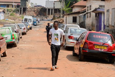 CENTRAL REGION, GHANA - Jan 17, 2017: Unidentified Ghanaian man in white shirt walks along the road in local village. People of Ghana suffer of poverty due to the bad economy Editorial