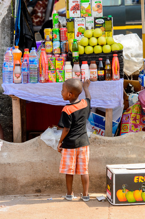 CENTRAL REGION, GHANA - Jan 17, 2017: Unidentified Ghanaian little boy stand in front of the counter  in local village. Children of Ghana suffer of poverty due to the bad economy Editorial