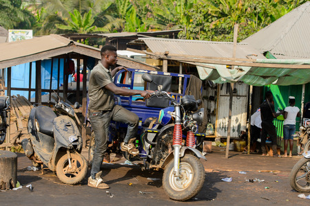 CENTRAL REGION, GHANA - Jan 17, 2017: Unidentified Ghanaian man tries to sit on tricycle in local village. People of Ghana suffer of poverty due to the bad economy Editoriali