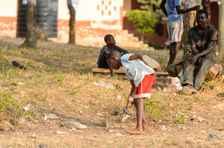 CENTRAL REGION, GHANA - Jan 17, 2017: Unidentified Ghanaian little boy bends down for something in local village. Children of Ghana suffer of poverty due to the bad economy