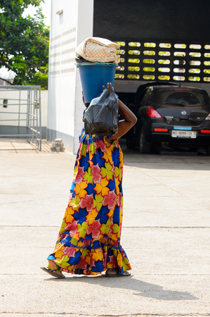 CENTRAL REGION, GHANA - Jan 17, 2017: Unidentified Ghanaian woman carries a bucket and plastic bag in local village. People of Ghana suffer of poverty due to the bad economy
