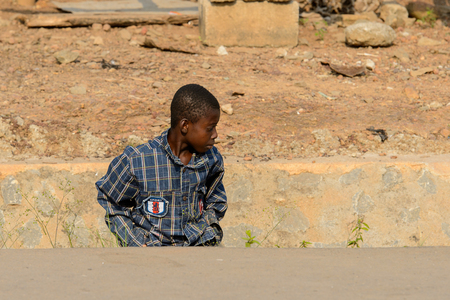 CENTRAL REGION, GHANA - Jan 17, 2017: Unidentified Ghanaian boy in plaid shirt looks down in local village. Children of Ghana suffer of poverty due to the bad economy