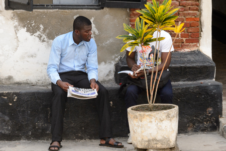 ELMINA, GHANA -JAN 18, 2017: Unidentified  Ghanaian men talk about something behind the flowerpot. People of Ghana suffer of poverty due to the bad economy
