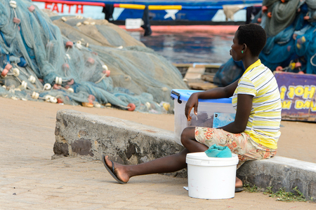 ELMINA, GHANA -JAN 18, 2017: Unidentified  Ghanaian woman rests from work in Elmina port. People of Ghana suffer of poverty due to the bad economy Editorial