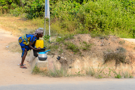 CENTRAL REGION, GHANA - Jan 17, 2017: Unidentified Ghanaian woman picks up a basin in local village. People of Ghana suffer of poverty due to the bad economy