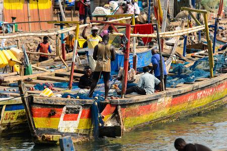 ELMINA, GHANA -JAN 18, 2017: Unidentified  Ghanaian people work in Elmina port. People of Ghana suffer of poverty due to the bad economy