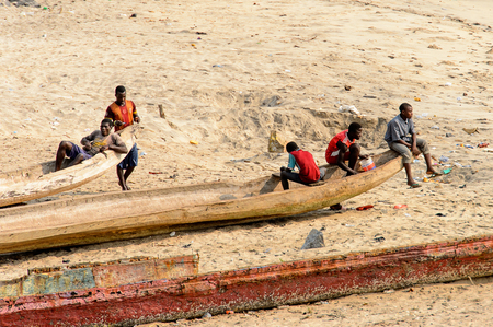 ELMINA, GHANA -JAN 18, 2017: Unidentified  Ghanaian people of different age hang out on the coast of Elmina near the wooden boat. People of Ghana suffer of poverty due to the bad economy