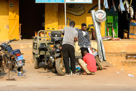 CENTRAL REGION, GHANA - Jan 17, 2017: Unidentified Ghanaian men repair a tricycle in local village. People of Ghana suffer of poverty due to the bad economy