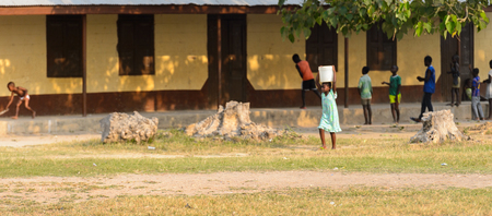 CENTRAL REGION, GHANA - Jan 17, 2017: Unidentified Ghanaian little girl carries a basin on her head in local village. Children of Ghana suffer of poverty due to the bad economy