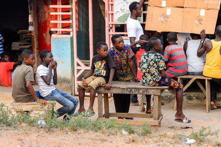CENTRAL REGION, GHANA - Jan 17, 2017: Unidentified Ghanaian boys sit on the wooden bench in local village. Children of Ghana suffer of poverty due to the bad economy