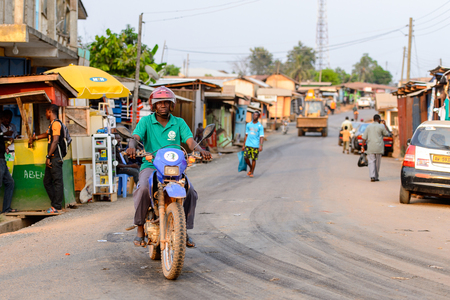 CENTRAL REGION, GHANA - Jan 17, 2017: Unidentified Ghanaian man rides a motorcycle in local village. People of Ghana suffer of poverty due to the bad economy Editoriali