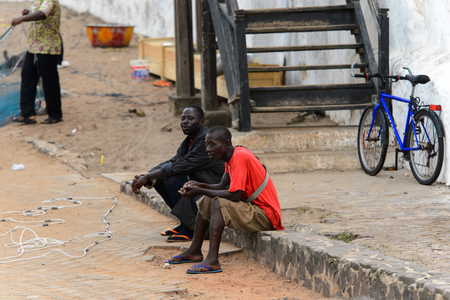 ELMINA, GHANA -JAN 18, 2017: Unidentified  Ghanaian men sit on the ground on the coast of Elmina. People of Ghana suffer of poverty due to the bad economy