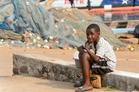 ELMINA, GHANA -JAN 18, 2017: Unidentified  Ghanaian little boy sits on the foundation next to the basin in Elmina port. Children of Ghana suffer of poverty due to the bad economy Stock Photo - 114099286