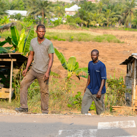 CENTRAL REGION, GHANA - Jan 17, 2017: Unidentified Ghanaian people walk near the road in local village. People of Ghana suffer of poverty due to the bad economy