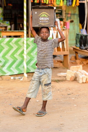 CENTRAL REGION, GHANA - Jan 17, 2017: Unidentified Ghanaian boy carries a paper box on his head in local village. Children of Ghana suffer of poverty due to the bad economy Editoriali